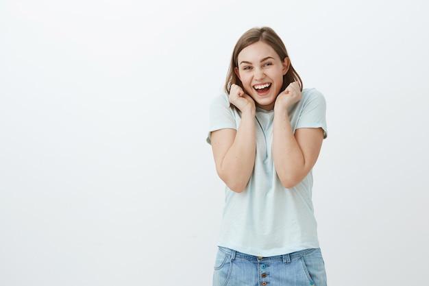 Mädchen, das zum ersten mal konzert besucht. charmante faszinierte und glückliche junge frau im trendigen t-shirt, die vor freude und aufregung schreit und hände in der nähe des gesichts hält, um auf großartige neuigkeiten zu reagieren Kostenlose Fotos