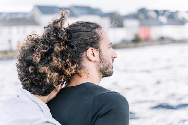 Mädchen, das zurück ihren partner mit dem meer unscharf umarmt Kostenlose Fotos