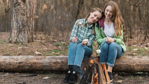Mädchen, die am lagerfeuer wärmen Kostenlose Fotos