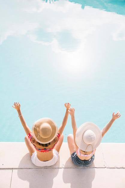 Mädchen, die arme vor pool anheben Kostenlose Fotos