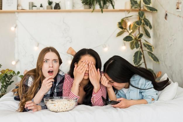 Mädchen, die auf dem bett liegen und popcorn essen und spaß haben Kostenlose Fotos