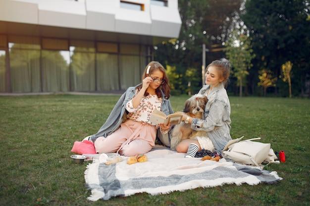 Mädchen, die auf einer decke in einem sommerpark sitzen Kostenlose Fotos