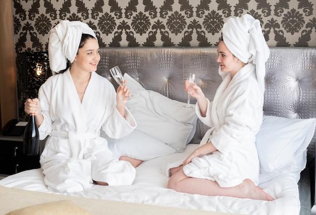 Mädchen, die badekurorttag mit einem glas champagner genießen Kostenlose Fotos