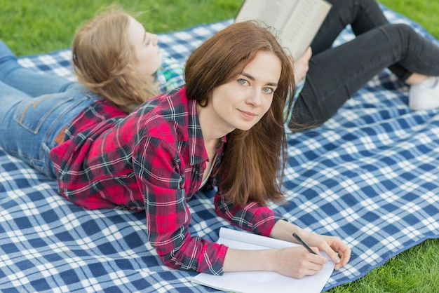 Mädchen, die hausaufgaben auf picknicktuch machen Kostenlose Fotos