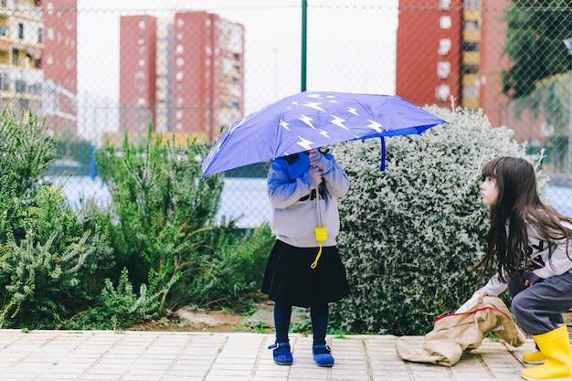 mädchen die mit regenschirm gehen  kostenlose foto
