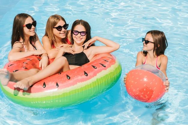 Mädchen, die mit wasserball und floatie spielen Kostenlose Fotos
