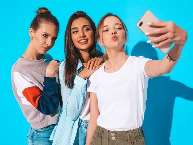 Mädchen, die selfie selbstporträtfotos auf smartphone machen modelle, die nahe blauer wand im studio aufwerfen frau, die entengesicht auf frontalkamera macht Kostenlose Fotos