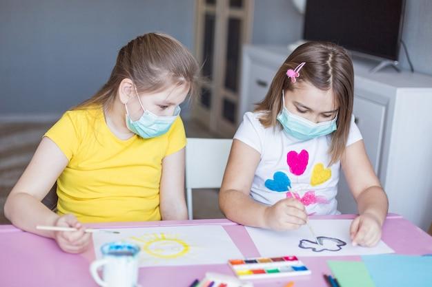 Mädchen, die zu hause während der quarantäne in sterilen masken zusammen zeichnen. kinderspiele, zeichenkunst, zu hause bleiben konzept Premium Fotos