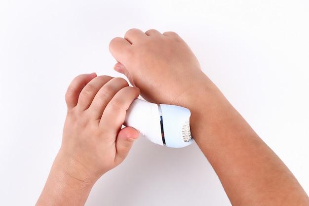 Mädchen entfernt haar mit elektrischem epilierer in ihren händen Premium Fotos
