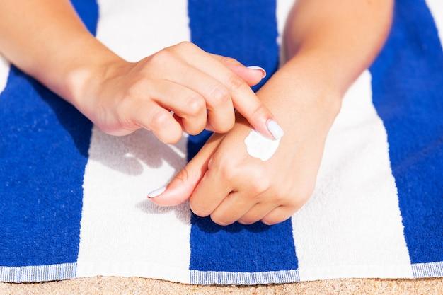 Mädchen entspannt sich auf dem handtuch auf dem sand am strand und trägt sonnencreme auf ihre hand auf Premium Fotos