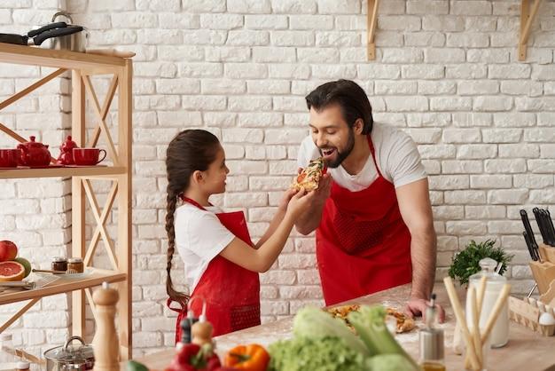 Mädchen füttert hungrigen vater mit einem stück pizza. Premium Fotos