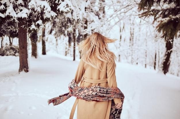 Mädchen geht in einem winterpark Kostenlose Fotos