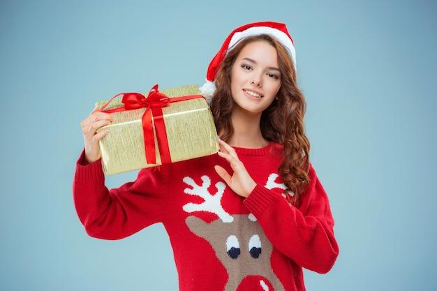 Mädchen gekleidet in weihnachtsmütze mit einem weihnachtsgeschenk. sie schaut in die kamera. urlaubskonzept mit blauem hintergrund. Kostenlose Fotos