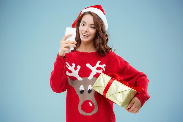 Mädchen gekleidet in weihnachtsmütze mit einem weihnachtsgeschenk und telefon. sie macht ein selfie-foto. urlaubskonzept mit blauem hintergrund. Kostenlose Fotos