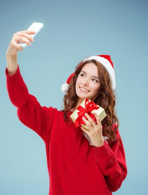Mädchen gekleidet in weihnachtsmütze mit einem weihnachtsgeschenk und telefon. Kostenlose Fotos