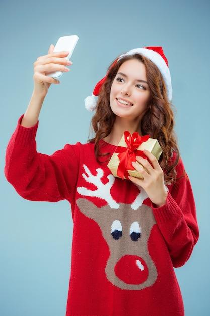 Mädchen gekleidet in weihnachtsmütze mit einem weihnachtsgeschenk und telefon Kostenlose Fotos