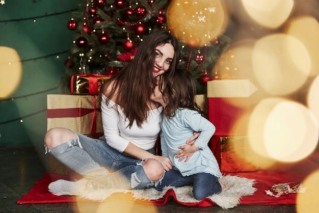 Mädchen gibt einen kuss. nette mutter und tochter, die nahe dem weihnachtsbaum das hinten sitzt Premium Fotos