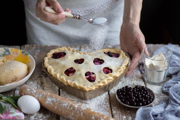 Mädchen gießt zucker zum backen. zucker mit obstkuchen bestreut. zu hause kochen. Premium Fotos