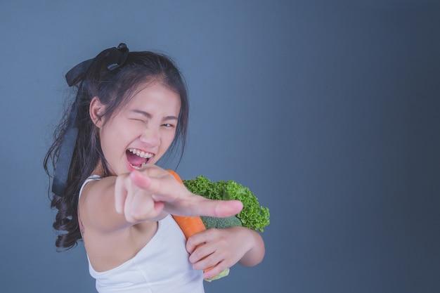 Mädchen hält das gemüse auf einem grauen hintergrund. Kostenlose Fotos