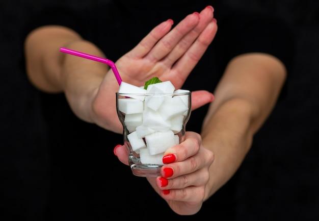 Mädchen hält ein glas gefüllt mit würfeln des weißen zuckers an, lehnt den gebrauch des zuckers ab Premium Fotos