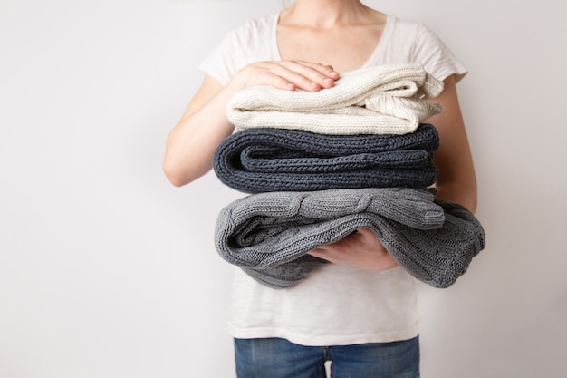 Mädchen hält einen stapel der gewaschenen und gebügelten kleidung gestrickten strickjacken in ihren händen Premium Fotos