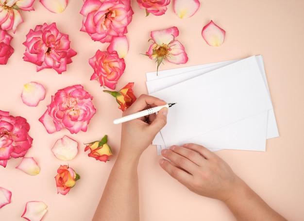 Mädchen hält in ihrer linken hand einen weißen stift und unterzeichnet umschläge auf einem pfirsichhintergrund Premium Fotos