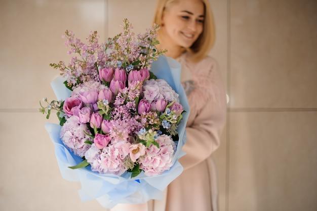 Mädchen hält strauß pfingstrosen, rosen und flieder Premium Fotos