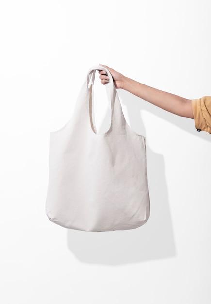 Mädchen hält taschensegeltuchgewebe für leere schablone des modells auf weißem hintergrund Premium Fotos