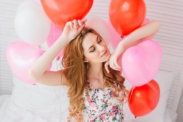 Mädchen im romantischen kleid mit ballonen in form eines herzens Premium Fotos
