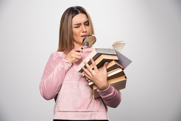 Mädchen im rosa swaetshirt, das einen vorrat an büchern hält und versucht, das oberste mit einer lupe zu lesen. Kostenlose Fotos