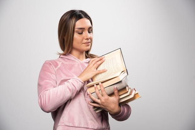 Mädchen im rosa swaetshirt hält einen vorrat an büchern, öffnet einen oben und liest ihn. Kostenlose Fotos