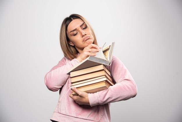 Mädchen im rosa swaetshirt hält einen vorrat an büchern, öffnet einen oben und liest ihn Kostenlose Fotos