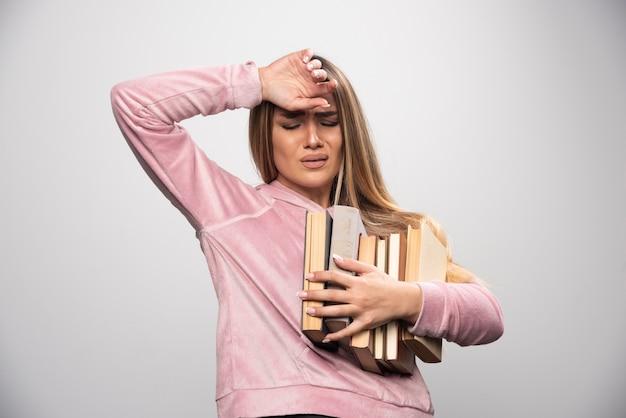 Mädchen im rosa swaetshirt hält einen vorrat an büchern und fühlt sich müde Kostenlose Fotos