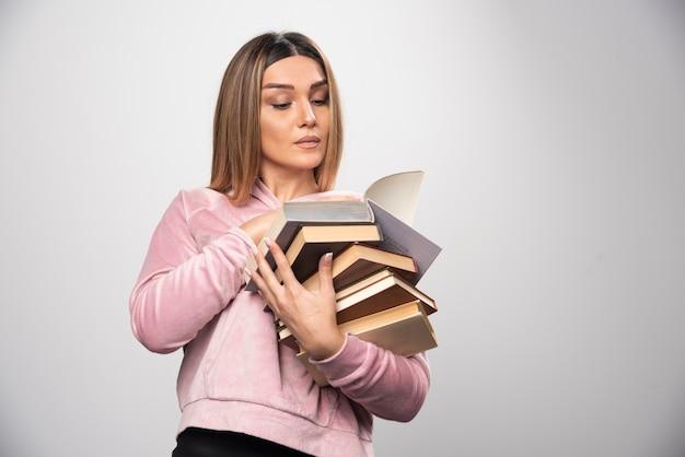 Mädchen im rosa sweatshirt hält einen vorrat an büchern, öffnet einen oben und liest ihn. Kostenlose Fotos