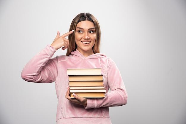 Mädchen im rosa sweatshirt hält einen vorrat an büchern und fühlt sich schlau. Kostenlose Fotos
