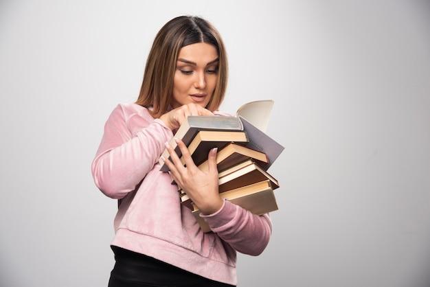 Mädchen im rosa sweatshirt hält einen vorrat an büchern und versucht, das oberste mit einer lupe zu lesen. Kostenlose Fotos