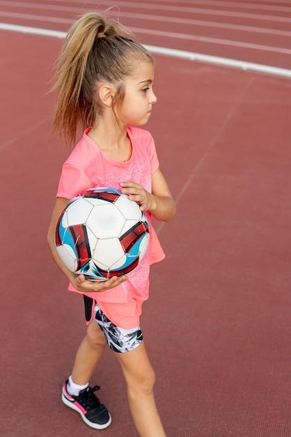 Mädchen im rosafarbenen t-shirt, das eine kugel anhält Kostenlose Fotos
