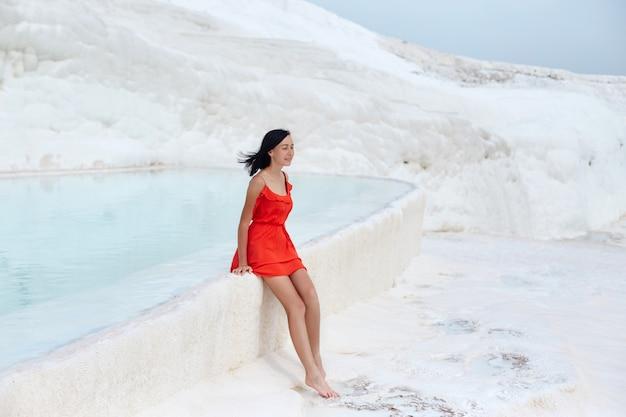 Mädchen im roten kleid auf weißen travertinen Premium Fotos