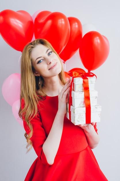 Mädchen im roten kleid hält kästen mit geschenken Premium Fotos