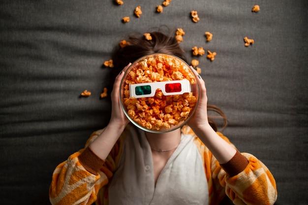 Mädchen im schlafanzug isst popcorn, liegt auf einem grauen hintergrund in 3d-brille und schaut sich einen film an Premium Fotos
