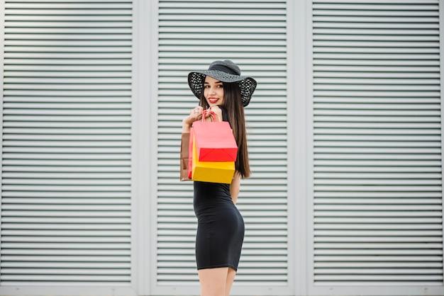 Mädchen im schwarzen kleid mit einkaufstüten Kostenlose Fotos
