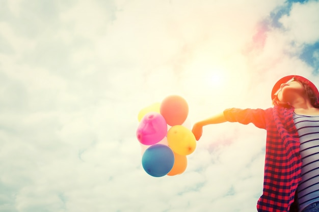Mädchen im sonnenuntergang mit luftballons Kostenlose Fotos