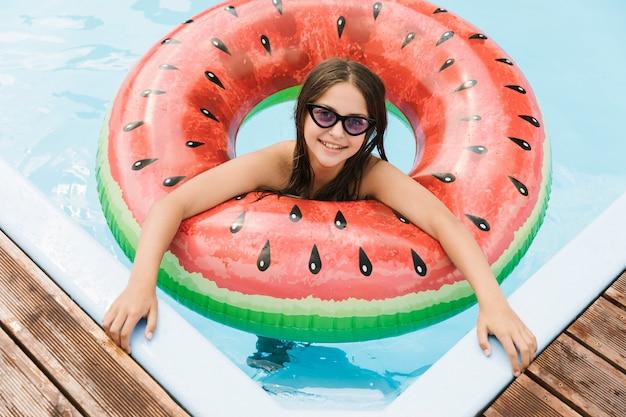 Mädchen im swimmingpool mit wassermelone floatie Kostenlose Fotos