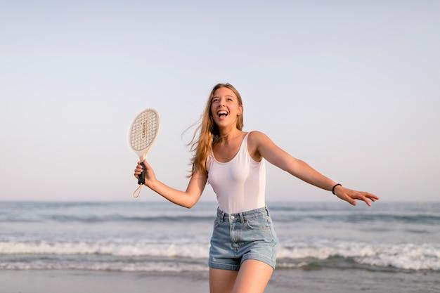 Mädchen im trägershirt und in den kurzschlüssen, die tennis an der küste spielen Kostenlose Fotos