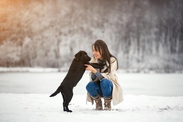 Mädchen im winter, der mit hund spielt Kostenlose Fotos
