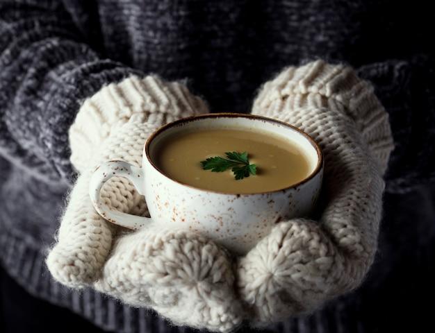 Mädchen in den handschuhen, die eine schale suppe anhalten Premium Fotos