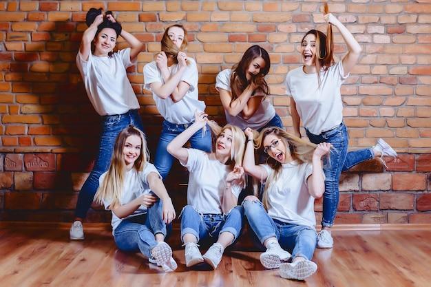 Mädchen in den jeans am hintergrund der backsteinmauer Premium Fotos