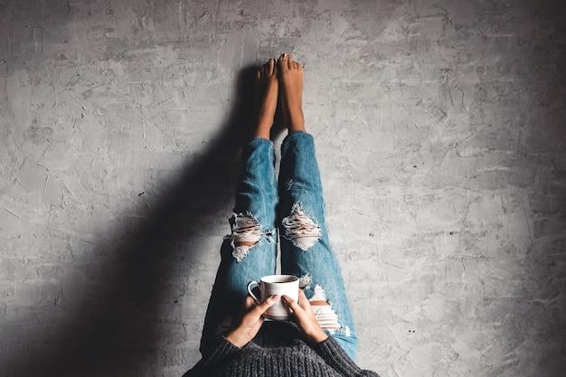 Mädchen in den jeans auf einem grauen hintergrund mit kaffee. liest ein buch mit den beinen an der wand. bildung, entwicklung. Premium Fotos