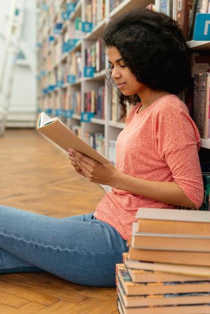 Mädchen in der bibliothek auf dem boden lesen Kostenlose Fotos