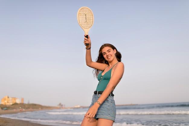 Mädchen in der bikinioberseite und in den kurzen hosen, die schläger am strand halten Kostenlose Fotos